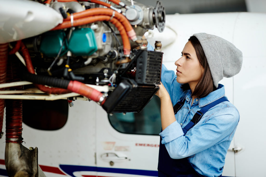 Photo of a young woman engineer who is fixing the motor on an airplane