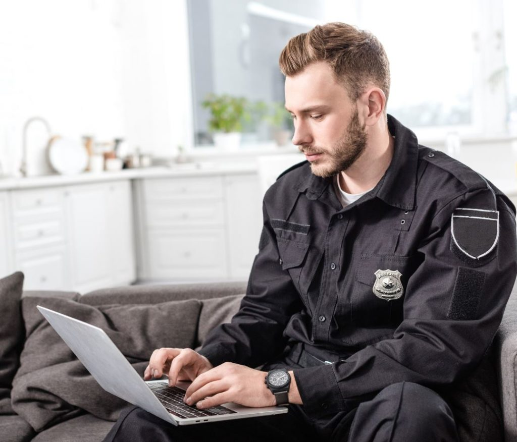 What technology has affected the criminal justice system. Officer on laptop